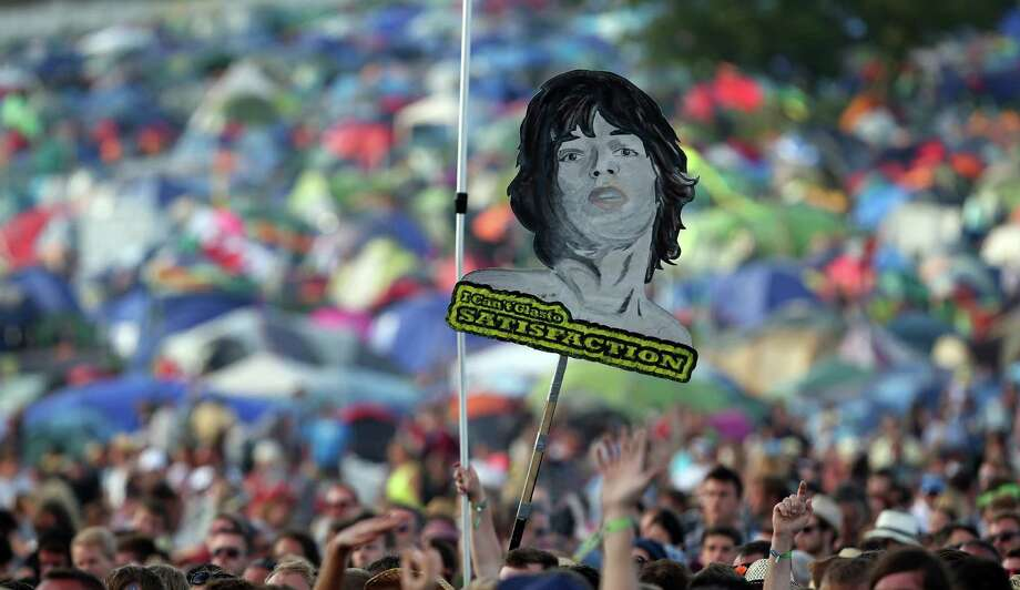 Music fans hold up a poster of Mick Jagger at the Glastonbury Festival of Contemporary Performing Arts site at Worthy Farm, Pilton on June 29, 2013 near Glastonbury, England. The wholesale market caters for traders throughout the Festival who are estimated to provide 3 million meals for festival goers, crew and performers. Gates opened on Wednesday at the Somerset diary farm that will be playing host to one of the largest music festivals in the world and this year features headline acts Artic Monkeys, Mumford and Sons and the Rolling Stones. Tickets to the event which is now in its 43rd year sold out in minutes and that was before any of the headline acts had been confirmed. The festival, which started in 1970 when several hundred hippies paid 1 GBP to watch Marc Bolan, now attracts more than 175,000 people over five days. Photo: Matt Cardy, Getty Images / 2013 Getty Images