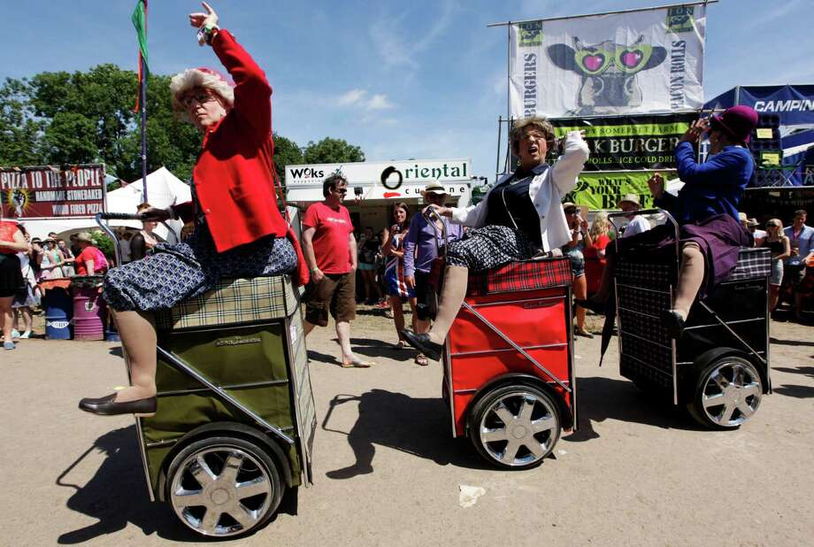 Men dressed in fancy dress ride in motorized shopping carts at Glastonbury, England on Saturday, June 29, 2013.  Thousands are to arrive for the three day festival that starts on Friday, June 28 2013 with headliners, Arctic Monkeys, the Rolling Stones and Mumford and Sons. Photo: Jim Ross, Associated Press / Invision