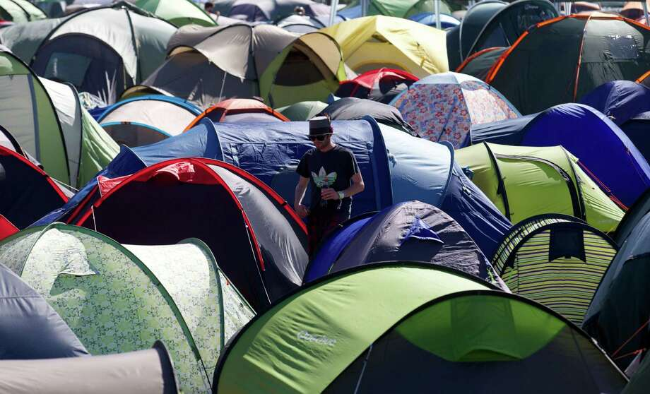 A Festival goers walks amongst tents on the fourth day of the Glastonbury Festival of Contemporary Performing Arts near Glastonbury, southwest England on June 29, 2013. The sun was out for Britain's world-renowned Glastonbury festival, drying the mud underfoot as tens of thousands waited for the first ever performance here by the Rolling Stones. Photo: ANDREW COWIE, AFP/Getty Images / AFP ImageForum
