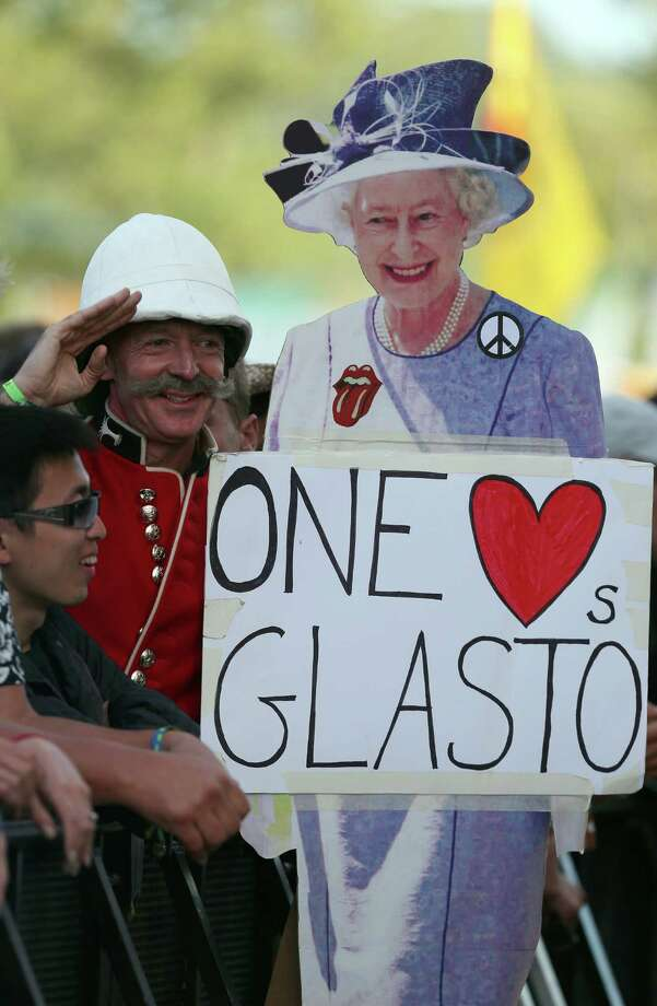 A man dressed in traditional army uniform salutes as he holds cardboard cutout of the Queen at the Glastonbury Festival of Contemporary Performing Arts site at Worthy Farm, Pilton on June 29, 2013 near Glastonbury, England. The wholesale market caters for traders throughout the Festival who are estimated to provide 3 million meals for festival goers, crew and performers. Gates opened on Wednesday at the Somerset diary farm that will be playing host to one of the largest music festivals in the world and this year features headline acts Artic Monkeys, Mumford and Sons and the Rolling Stones. Tickets to the event which is now in its 43rd year sold out in minutes and that was before any of the headline acts had been confirmed. The festival, which started in 1970 when several hundred hippies paid 1 GBP to watch Marc Bolan, now attracts more than 175,000 people over five days. Photo: Matt Cardy, Getty Images / 2013 Getty Images