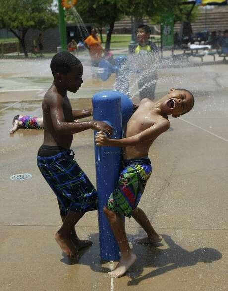 Children play with a water cannon at Tempe Beach Park in Tempe, Ariz. Excessive heat warnings will continue for much of the Southwest as building high pressure triggers major warming. Photo: Rick Scuteri / Associated Press