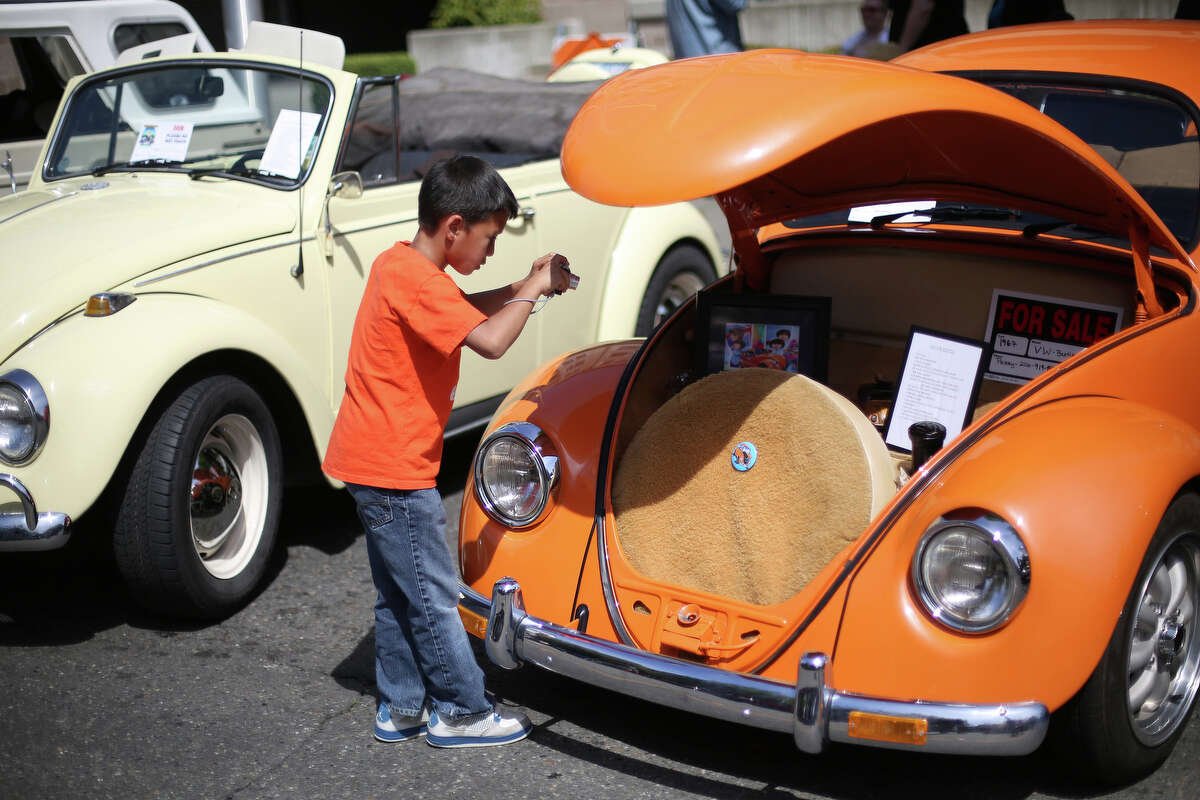 Jordan Stroud, 7, takes a photo of a VW bug during the Greenwood Car Show on Saturday, June 29, 2013 in Seattle. The annual show is the largest single-day car show in the state.