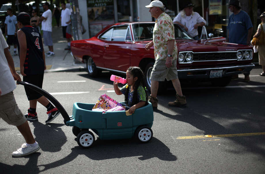 People make their way along Greenwood Avenue North during the Greenwood Car Show on Saturday, June 29, 2013 in Seattle. The annual show is the largest single-day car show in the state. Photo: JOSHUA TRUJILLO, SEATTLEPI.COM