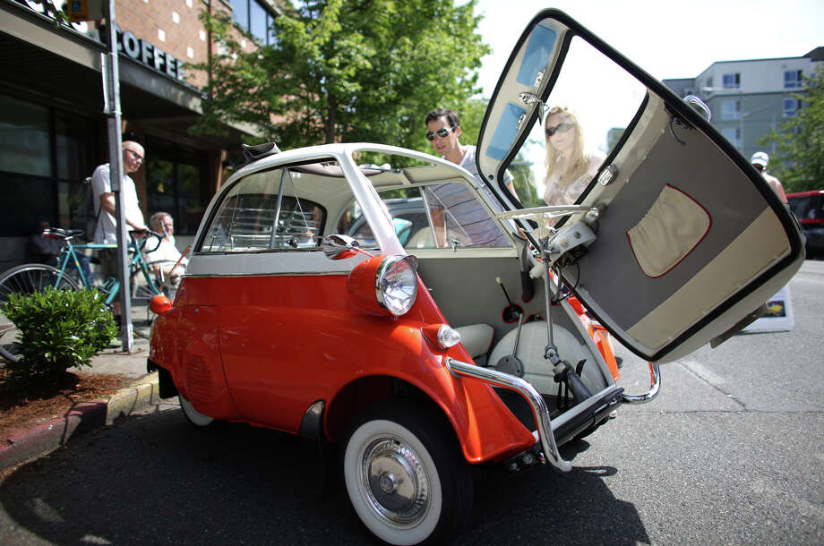 People look over a BMW Isetta 300 on Greenwood Avenue North during the Greenwood Car Show on Saturday, June 29, 2013 in Seattle. The annual show is the largest single-day car show in the state. Photo: JOSHUA TRUJILLO, SEATTLEPI.COM