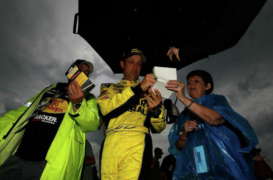 Since the Sprint Cup race at Kentucky Speedway was postponed until Sunday afternoon, driver Matt Kenseth (center) has time to sign autographs. Photo: Kevin C. Cox / Getty Images