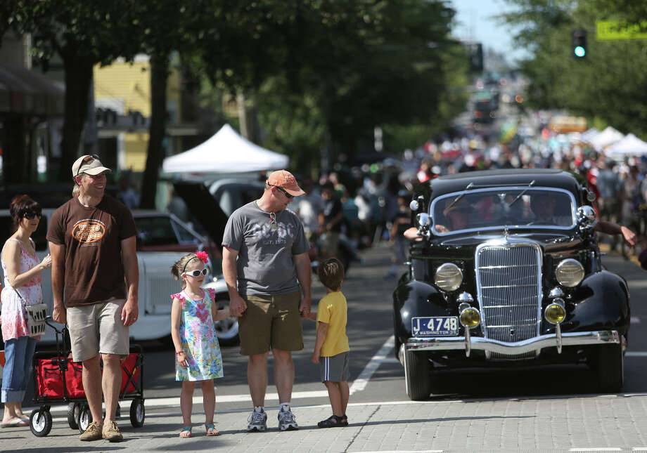 People prepare to cross N 85th Street during the Greenwood Car Show on Saturday, June 29, 2013 in Seattle. The annual show is the largest single-day car show in the state. Photo: JOSHUA TRUJILLO, SEATTLEPI.COM