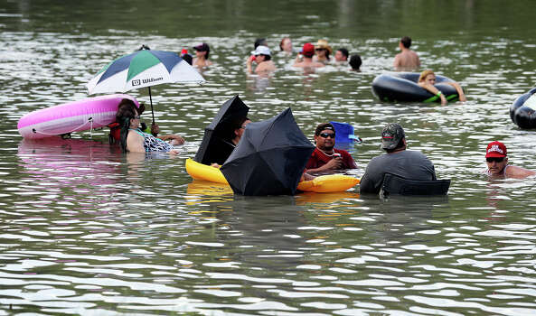 Keeping some shade with umbrellas, recreationalists hit the waters of the Guadalupe River near New Braunfels  on June 29, 2013. Photo: TOM REEL