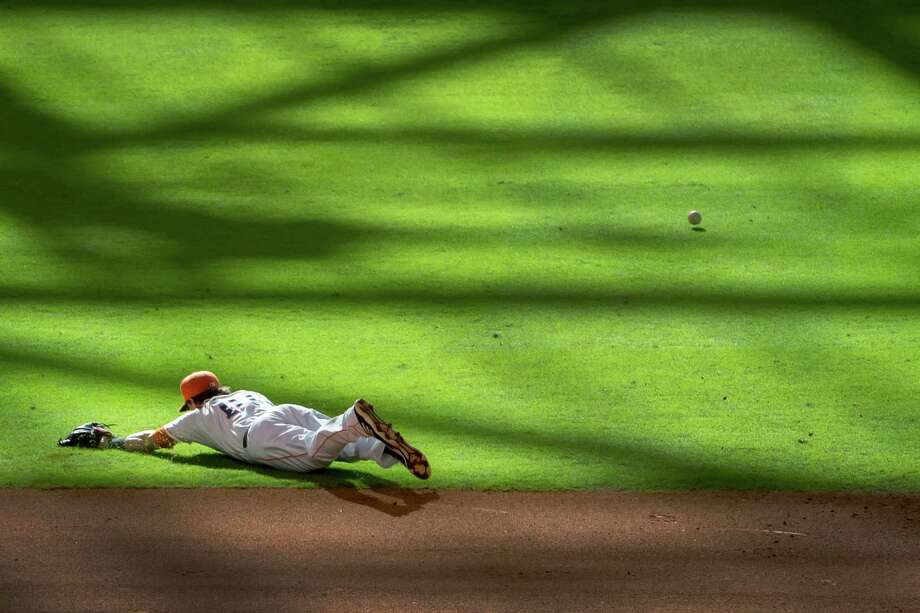 Astros shortstop Jake Elmore can't make the play on a single by the Angels' Mark Trumbo during the ninth inning at Minute Maid Park on Saturday. It was a tough day for Elmore (0-for-4 with two errors) and the Astros (a 7-2 loss, their 51st of 2013). Photo: Smiley N. Pool / © 2013  Smiley N. Pool