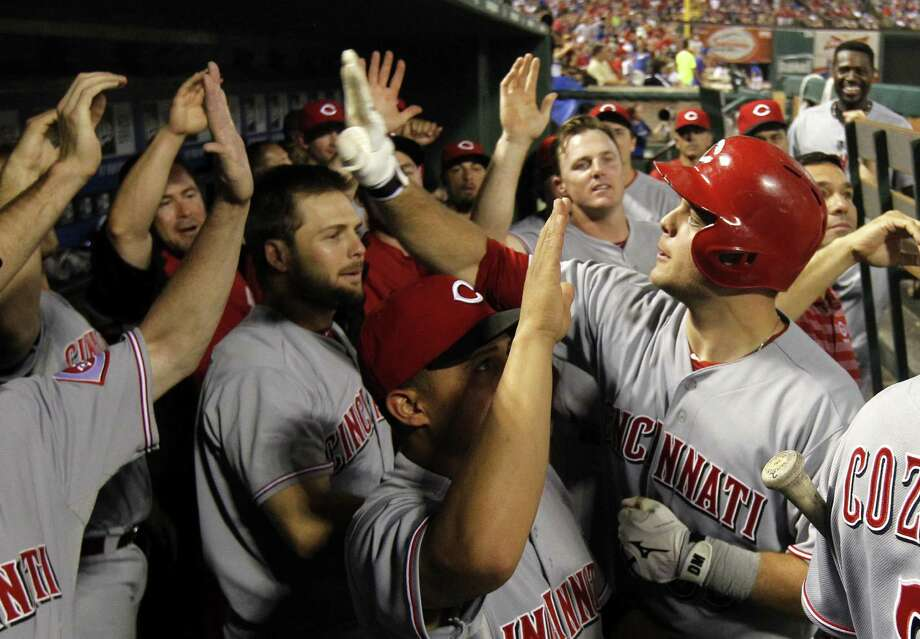 Cincinnati's Devin Mesoraco (right) exchanges high-fives after his 11th-inning, two-run homer. Photo: Tony Gutierrez / Associated Press