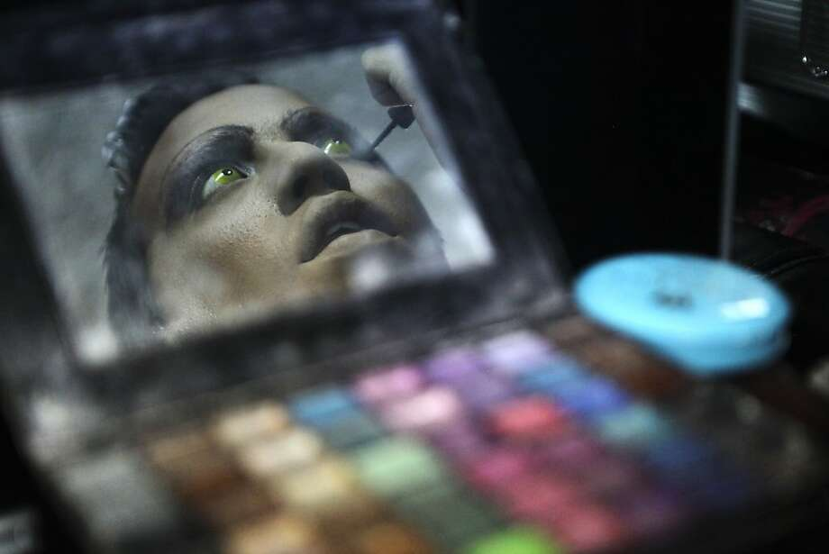 "Drag queen ""Giva Queen"" makes final adjustments to her make-up inside a bar before going to the annual Gay Pride Parade in Lima, Peru, Saturday, June 29, 2013. Gays, lesbians and transgenders are participating in gay pride parades worldwide in late June as part of annual demonstrations for equal rights and against discrimination. (AP Photo/Karel Navarro) Photo: Karel Navarro, Associated Press"