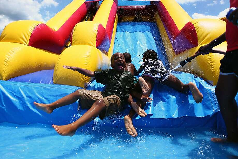 Aiden Johnson, left, Malik Morgan, center, and Mariah Williams enjoy an inflatable water slide at the 1st Juneteenth Family Fun Festival sponsored by the DeSoto County African American History Symposium at Latimer Lakes Park in Horn Lake, Miss. Saturday, June 29, 2013. (AP Photo/The Commercial Appeal, Kyle Kurlick) Photo: Kyle Kurlick, Associated Press