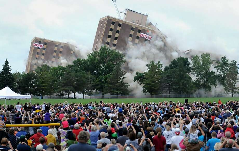 Thousands watch as Gage Towers on the Minnesota State University, Mankato campus collapse onto themselves seconds after series of strategic explosive charges were set off Saturday, June 29, 2013. The site will be redeveloped for parking. Two new buildings have already replaced the dormitory, after the university decided it was cheaper to build new, more modern on-campus housing than rehabilitate the old complex. School officials estimate the Gage Towers were home to more than 50,000 students since they opened in 1965. The complex closed last August after the Minnesota Vikings' training camp.  (AP Photo/The Mankato Free Press, John Cross) Photo: John Cross, Associated Press