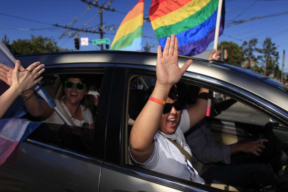 Adri Galvan waves out of a car in San Francisco's Castro district after the Supreme Court of the United States both dismissed Proposition 8  and ruled the Defense of Marriage Act unconstitutional on Wednesday June 26, 2013 in San Francisco, Calif.