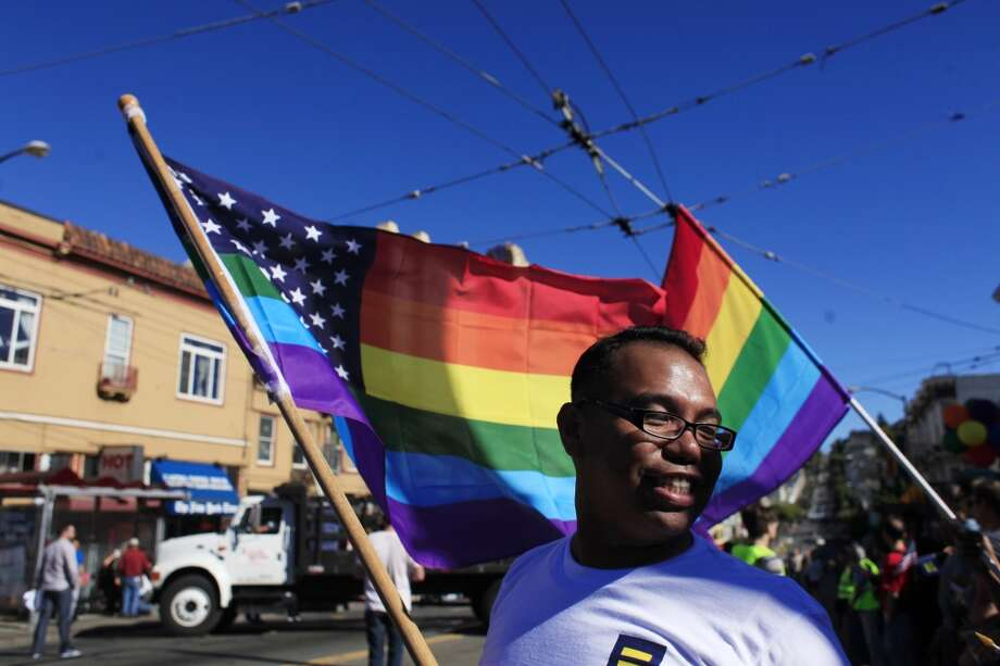 Larry Pasqua waves a rainbow flag in San Francisco's Castro district after the Supreme Court of the United States both dismissed Proposition 8  and ruled the Defense of Marriage Act unconstitutional on Wednesday June 26, 2013 in San Francisco, Calif.
