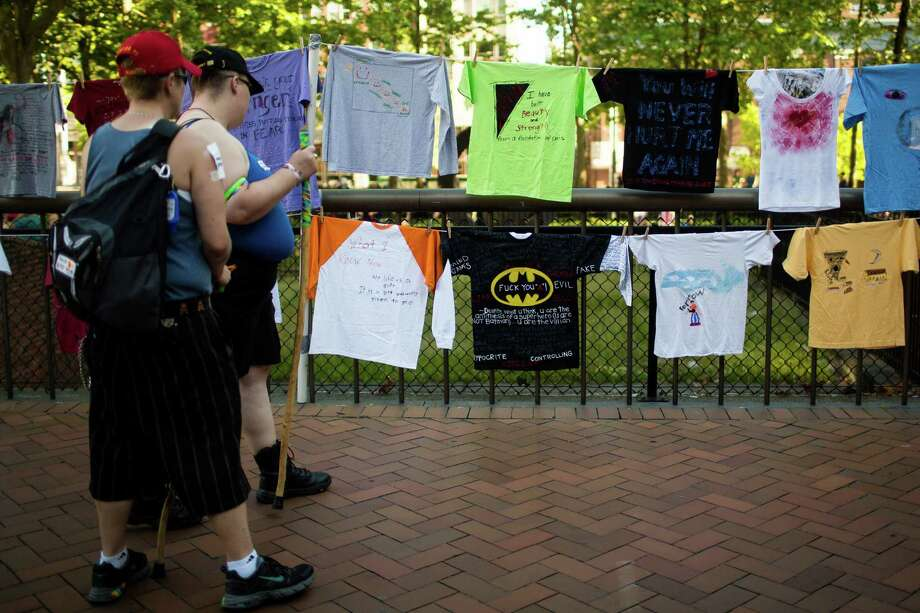 Marchers pause to take in T-shirts with handwritten messages scrawled upon them before the Seattle Dyke March Saturday, June 29, 2013, in Seattle. The march, held every year, intends to increase lesbian visibility and activism without focusing on labels, such as bisexual, intersex and transgendered women. Photo: JORDAN STEAD, SEATTLEPI.COM / JORDAN STEAD