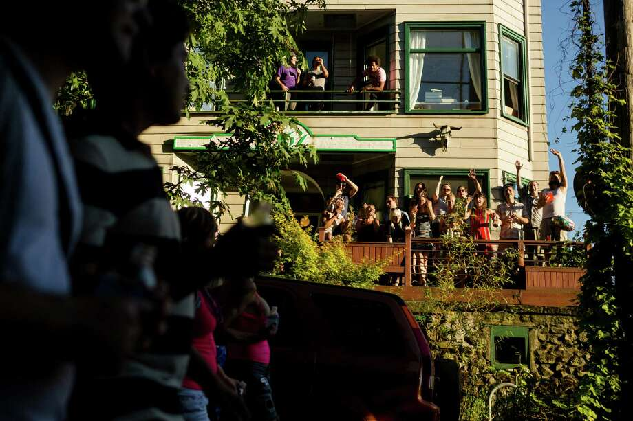 Households of partiers cheer on marchers from their porch during the Seattle Dyke March Saturday, June 29, 2013, in Seattle. The march, held every year, intends to increase lesbian visibility and activism without focusing on labels, such as bisexual, intersex and transgendered women. Photo: JORDAN STEAD, SEATTLEPI.COM / JORDAN STEAD