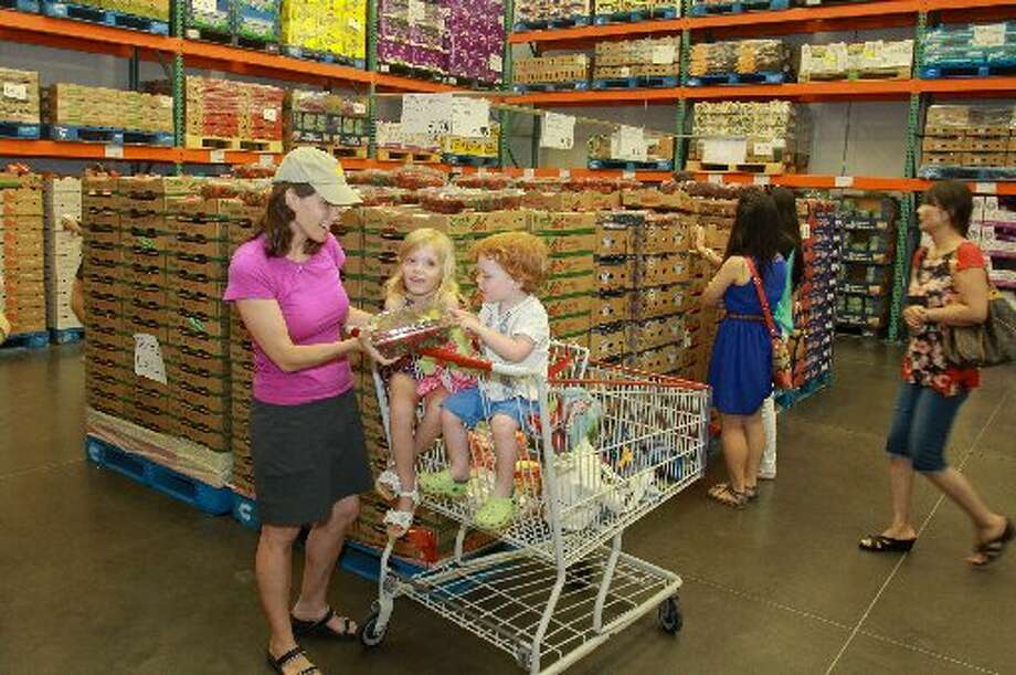 Jennifer Tellepsen shopping with her children, Ruby, 5, and Henry 2, in the fresh produce cooler at Costco.