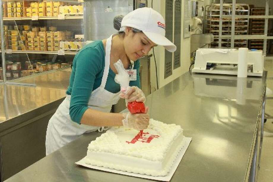 Lucy Lopez decorating a bakery cake at Costco.