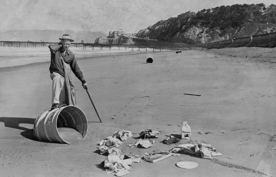 Fred Rotherwell, beach attendant, cleaning up overturned trash cans on Ocean Beach, August 25, 1960.