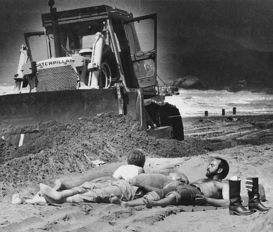 Some sun bathers couldn't seem to find the right spot on the beach, while a bulldozer was moving the sand. April 2, 1983. Ocean Beach
