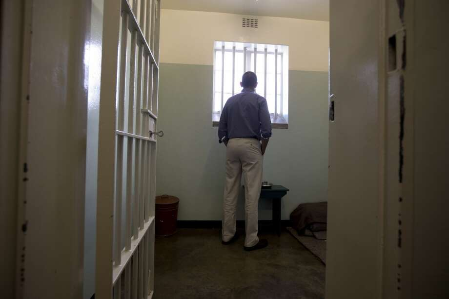 RETRANSMISSIU.S. President Barack Obama peers out from Section B, prison cell No. 5, on Robben Island, South Africa, Sunday, June 30, 2013.  This was former South African president Nelson Mandela's cell.