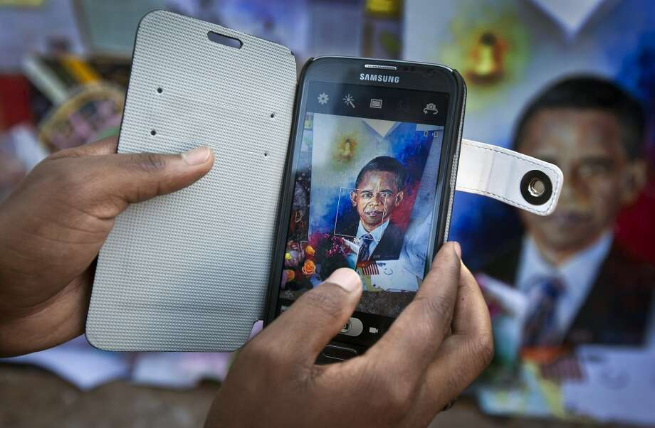A wellwisher takes a photograph with their smartphone of a painting of President Barack Obama that sits amongst get-well messages and images of former South African President Nelson Mandela outside the Mediclinic Heart Hospital where Nelson Mandela is being treated in Pretoria, South Africa Saturday, June 29, 2013.