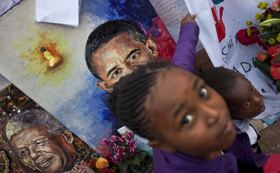 Children squat to have their photograph taken by their parents next to paintings of President Barack Obama, center, and former South African President Nelson Mandela, left, outside the Mediclinic Heart Hospital where Nelson Mandela is being treated in Pretoria, South Africa Saturday, June 29, 2013.