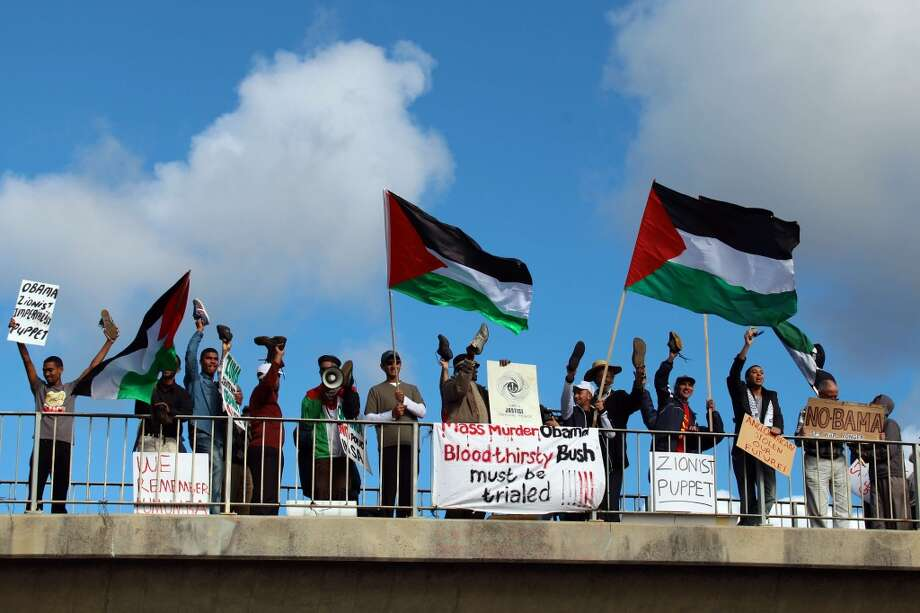 Protesters wave their shoes and the Palestinian flag during a demonstration against the visit of US President Barack Obama outside the University of Cape Town in South Africa on June 30, 2013.