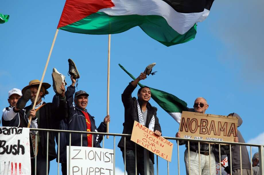 Protesters wave their shoes and the Palestinian flag.