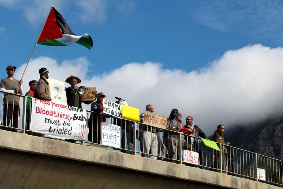 Protesters hold signs and the Palestinian flag during a demonstration against the visit of U.S. President Barack Obama in South Africa on June 30, 2013.