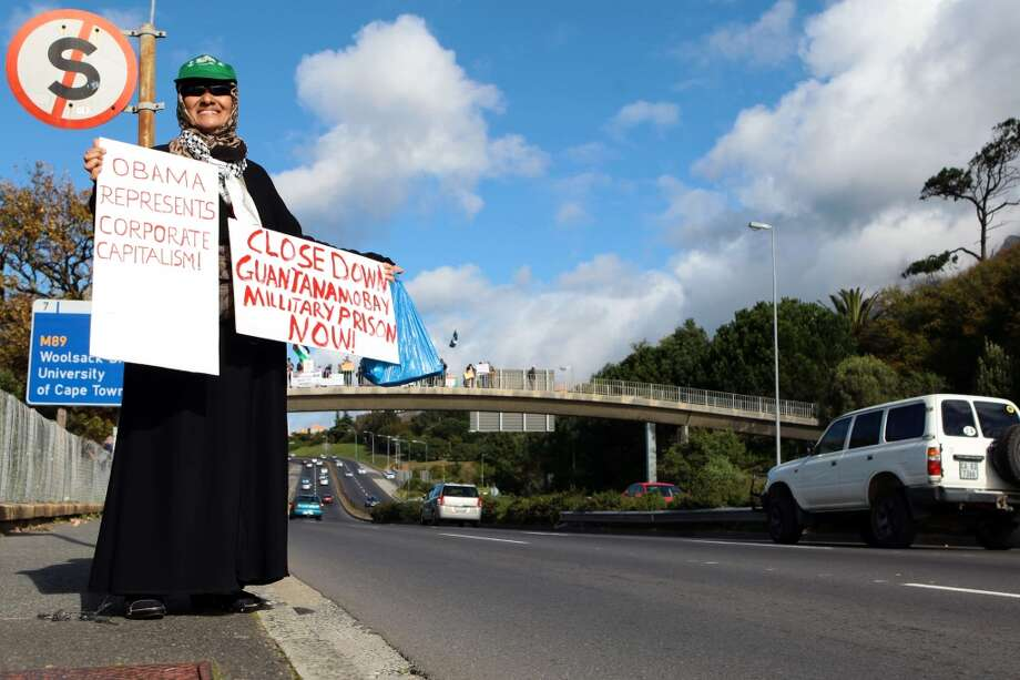 A veiled protestor hold signs during a demonstration against the visit of US President Barack Obama outside the University of Cape Town (UCT) in South Africa on June 30, 2013. Obama is due to speak at UCT this evening on the last day of his state visit to South Africa. AFP PHOTO/JENNIFER BRUCEJENNIFER BRUCE/AFP/Getty Images