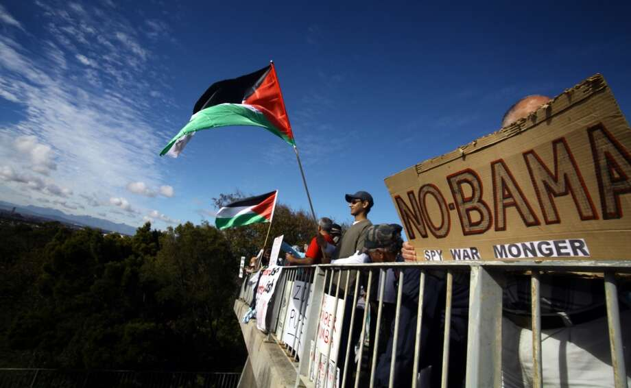Protestors hold signs and Palestinian flags during a demonstration against the visit of US President Barack Obama outside the University of Cape Town (UCT) in South Africa on June 30, 2013. Obama is due to speak at UCT this evening on the last day of his state visit to South Africa. AFP PHOTO/STRINGER-/AFP/Getty Images