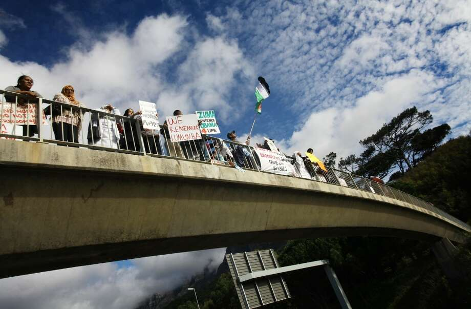 Protestors hold signs and Palestinian flags during a demonstration on an overpass bridge on the M3 against the visit of US President Barack Obama outside the University of Cape Town (UCT) in South Africa on June 30, 2013. Obama is due to speak at UCT this evening on the last day of his state visit to South Africa. AFP PHOTO/STRINGER-/AFP/Getty Images