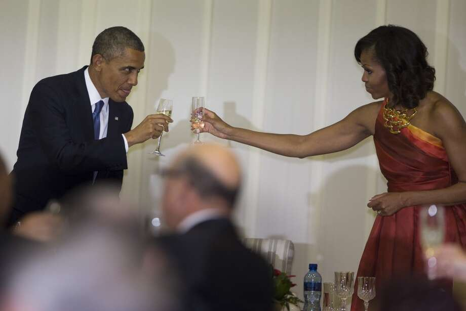 U.S. President Barack Obama and first lady Michelle Obama toast during an official dinner hosted by South African President Jacob Zuma at the Presidential Guest House on Saturday, June 29, 2013, in Pretoria, South Africa. The visit comes at a poignant time, with former South African president and anti-apartheid hero Nelson Mandela ailing in a Johannesburg hospital. (AP Photo/Evan Vucci)