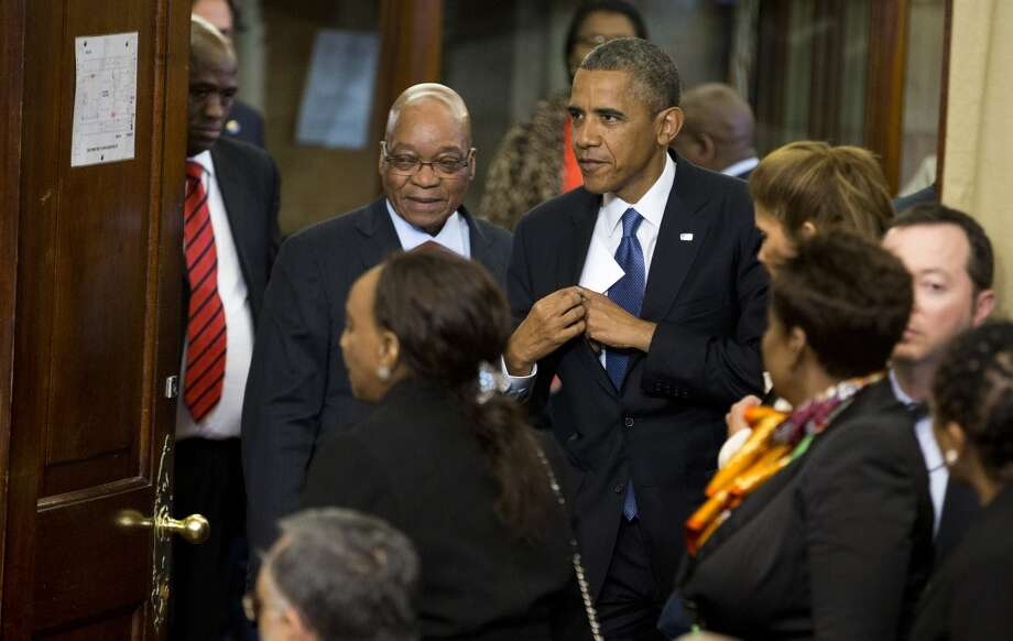 "U.S. President Barack Obama, centre right, arrives for a news conference with South African President Jacob Zuma, centre left, at the Union Building on Saturday, June 29, 2013, in Pretoria, South Africa.  The visit comes at a poignant time, with former South African president and anti-apartheid hero Nelson Mandela ailing in a Johannesburg hospital.  The White House issued a statement Saturday that President Barack Obama plans to visit privately with relatives of former South African President Nelson Mandela, but doesn't intend to see the critically ill anti-apartheid activist he has called a ""personal hero."" (AP Photo/Evan Vucci)"
