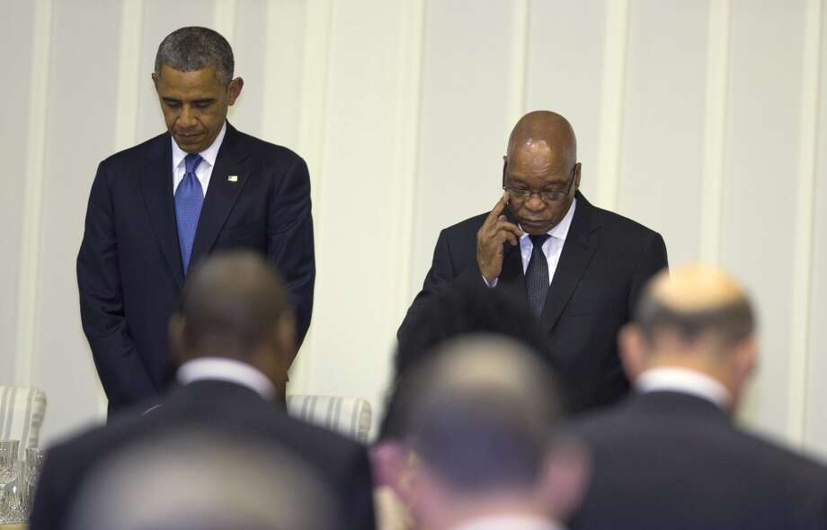 U.S. President Barack Obama, left, stands for a moment of silence for Nelson Mandela during an official dinner with South African President Jacob Zuma at the Presidential Guest House on Saturday, June 29, 2013, in Pretoria, South Africa. The visit comes at a poignant time, with former South African president and anti-apartheid hero Nelson Mandela ailing in a Johannesburg hospital. (AP Photo/Evan Vucci)