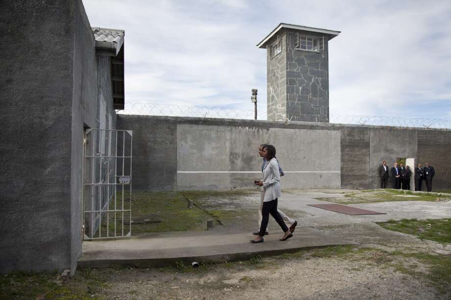 U.S. President Barack Obama, partially visible centerleft, and first lady Michelle Obama tour Robben Island, South Africa, Sunday, June 30, 2013. Robben Island is a historic Apartheid-era prison that held black political prisoners including former South African president and anti-apartheid hero Nelson Mandela. (AP Photo/Evan Vucci)