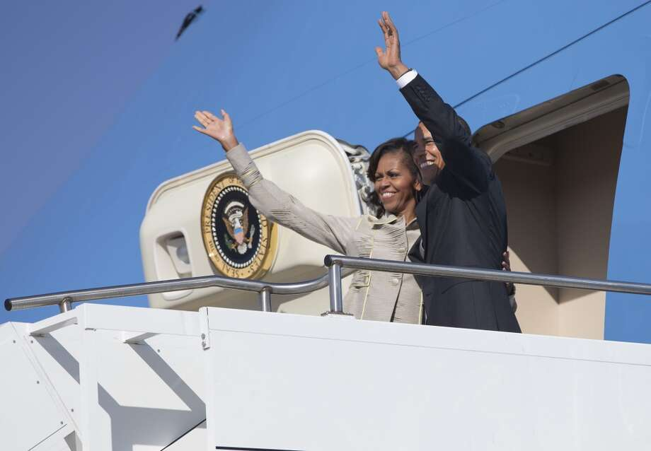 U.S. President Barack Obama and first lady Michelle Obama wave as they depart Waterkloof Air Base for a flight to Cape Town on Sunday, June 30, 2013, in Centurion, South Africa. The president is in South Africa, embarking on the second leg of his three-country African journey. The visit comes at a poignant time, with former South African president and anti-apartheid hero Nelson Mandela ailing in a Johannesburg hospital. (AP Photo/Evan Vucci)