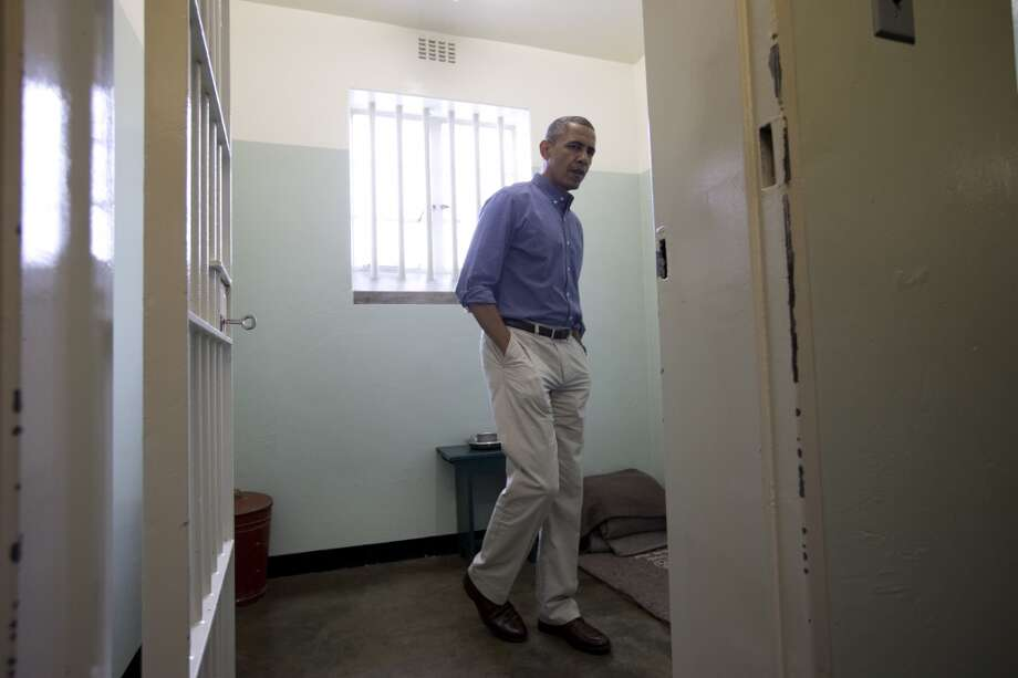 U.S. President Barack Obama looks out from Section B, prison cell No. 5, on Robben Island, South Africa, Sunday, June 30, 2013. This was former South African president Nelson Mandela's cell, where spent 18-years of his 27-year prison term on the island locked up by the former apartheid government. (AP Photo/Carolyn Kaster)