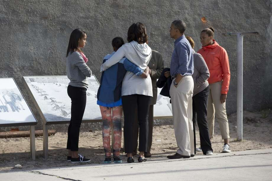 From left, Malia Obama, Sasha Obama, first lady Michelle Obama, Ahmed Kathrada former prisoner with Nelson Mandela guiding the tour, U.S. President Back Obama, Marian Robinson and Leslie Robinson, stand in the courtyard of the prison on Robben Island, South Africa, Sunday, June 30, 2013. Former South African president Nelson Mandela spent 18 years of his 27-year prison term on the island locked up by the former apartheid government. (AP Photo/Carolyn Kaster)