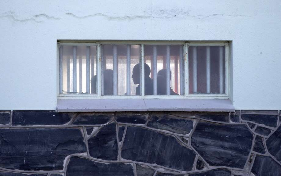 U.S. President Back Obama in silhouette, center, walks by a bar covered windows during a tour of the prison on Robben Island, South Africa, Sunday, June 30, 2013. Former South African president Nelson Mandela spent 18 years of his 27-year prison term on the island locked up by the former apartheid government. (AP Photo/Carolyn Kaster)