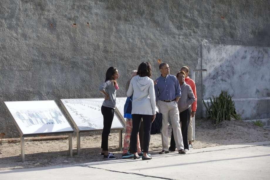 From left, Malia Obama, Sasha Obama, first lady Michelle Obama, U.S. President Back Obama, Marian Robinson and Leslie Robinson, stand in the courtyard of the prison on Robben Island,  South Africa, Sunday, June 30, 2013, during a tour guided by Ahmed Kathrada, who is a former prisoner with Nelson Mandela, in the back pointing. Former South African president Nelson Mandela spent 18 years of his 27-year prison term on the island locked up by the former apartheid government. (AP Photo/Carolyn Kaster)