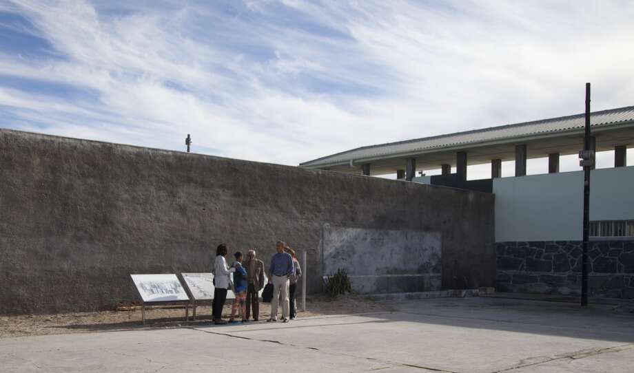 From left, first lady Michelle Obama, Sasha Obama, Ahmed Kathrada former prisoner with Nelson Mandela and guiding the tour, U.S. President Back Obama, Marian Robinson and Leslie Robinson, stand in the courtyard of the prison on Robben Island, South Africa, Sunday, June 30, 2013. Former South African president Nelson Mandela spent 18 years of his 27-year prison term on the island locked up by the former apartheid government. (AP Photo/Carolyn Kaster)