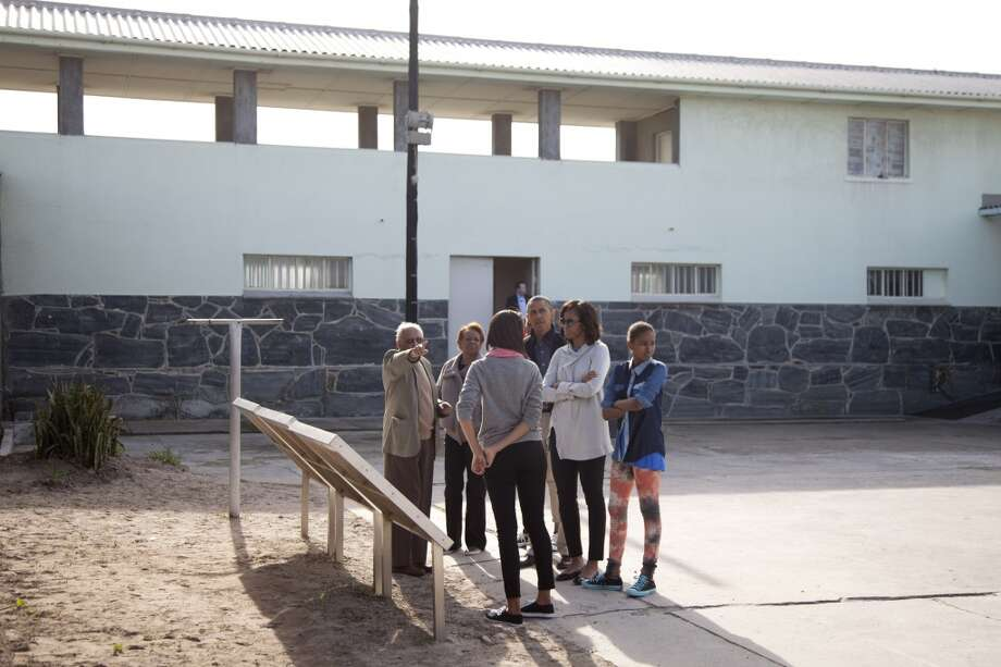From left, Ahmed Kathrada former prisoner with Nelson Mandela, points out into the courtyard as he gives a tour to Marian Robinson, Malia Obama, U.S. President Back Obama, first lady Michelle Obama and Sasha Obama of the prison on Robben Island, South Africa, Sunday, June 30, 2013. Former South African president Nelson Mandela spent 18 years of his 27-year prison term on the island locked up by the former apartheid government. (AP Photo/Carolyn Kaster)
