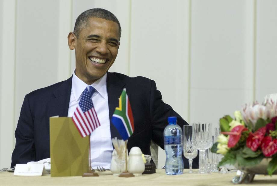 US President Barack Obama laughs during an official dinner hosted by the president of South Africa at the Presidential Guest House in Pretoria, South Africa, on June 29, 2013. AFP PHOTO / Saul LOEBSAUL LOEB/AFP/Getty Images