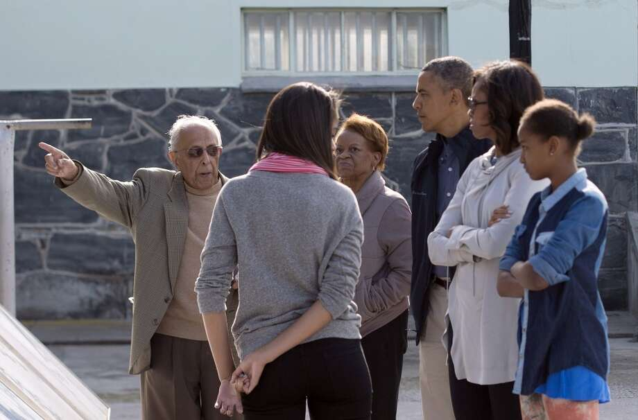 Ahmed Kathrada (L), a former prisoner with anti-apartheid activist Nelson Mandela, tours US President Barack Obama (3rdR) and his family through Robben Island, South Africa, on June 30, 2013. With Obama is his daughters Sasha (R) and Malia (C), First Lady Michelle Obama (2nd R) and his mother-in-law Marian Robinson (3rdL). Paying homage to the 94-year-old former South-African president, who is critically ill in hospital, Obama stared into the stark cell where Mandela spent two thirds of his 27 years in jail.  AFP PHOTO/JIM  WATSONJIM WATSON/AFP/Getty Images