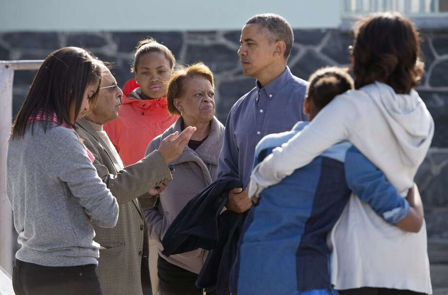 Ahmed Kathrada (L), a former prisoner with anti-apartheid activist Nelson Mandela gives a tour of the prison to US President Barack Obama (3rdR) and his family on Robben Island, South Africa on June 30, 2013. With Obama are his daughters Sasha (R) and Malia (L), First Lady Michelle Obama (R) and his mother-in-law Marian Robinson (C). Paying homage to the 94-year-old former South-African president, who is critically ill in hospital, Obama stared into the stark cell where Mandela spent two thirds of his 27 years in jail.  AFP PHOTO/JIM  WATSON  JIM WATSON/AFP/Getty Images