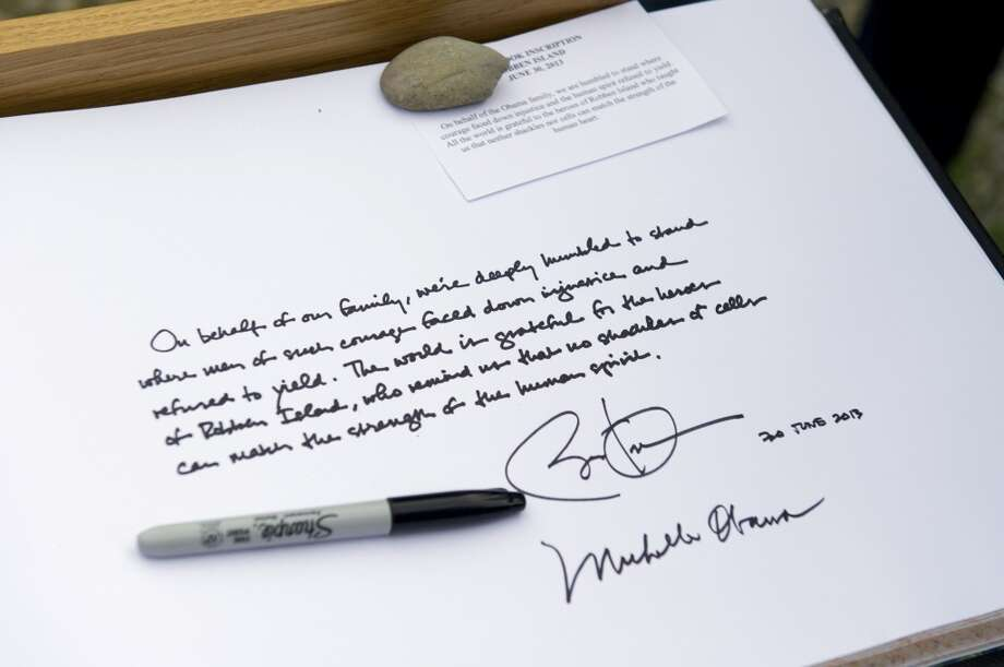 "A picture taken on June 30, 2013 shows the note that US President Barack Obama and First Lady Michelle Obama signed in a guestbook at Robben Island outside Cape Town, South Africa, on June 30, 2013. Obama was ""deeply humbled"" by a visit to the cell where Nelson Mandela spent years as a prisoner, in a solemn homage Sunday to the critically ill hero he was unable to see in Pretoria. AFP PHOTO / Saul LOEBSAUL LOEB/AFP/Getty Images"