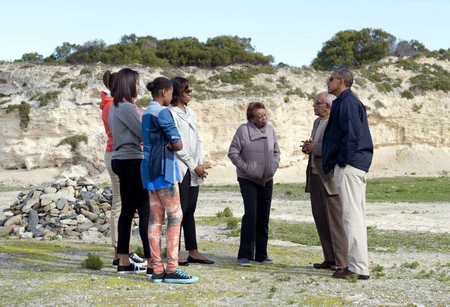 "US President Barack Obama (R), First Lady Michelle Obama (3L), their daughters Sasha (L), Malia (2L) and Michelle Obama's mother Marian Robinson (C) listen to former prisoner Ahmed Kathrada (2R) as they stand in the limestone quarry where prisoners worked on Robben Island off the coast of Cape Town, South Africa on June 30, 2013. President Barack Obama was ""deeply humbled"" by a visit to the cell where Nelson Mandela spent years as a prisoner, in a solemn homage Sunday to the critically ill hero he was unable to see in Pretoria. AFP PHOTO / Saul LOEBSAUL LOEB/AFP/Getty Images"