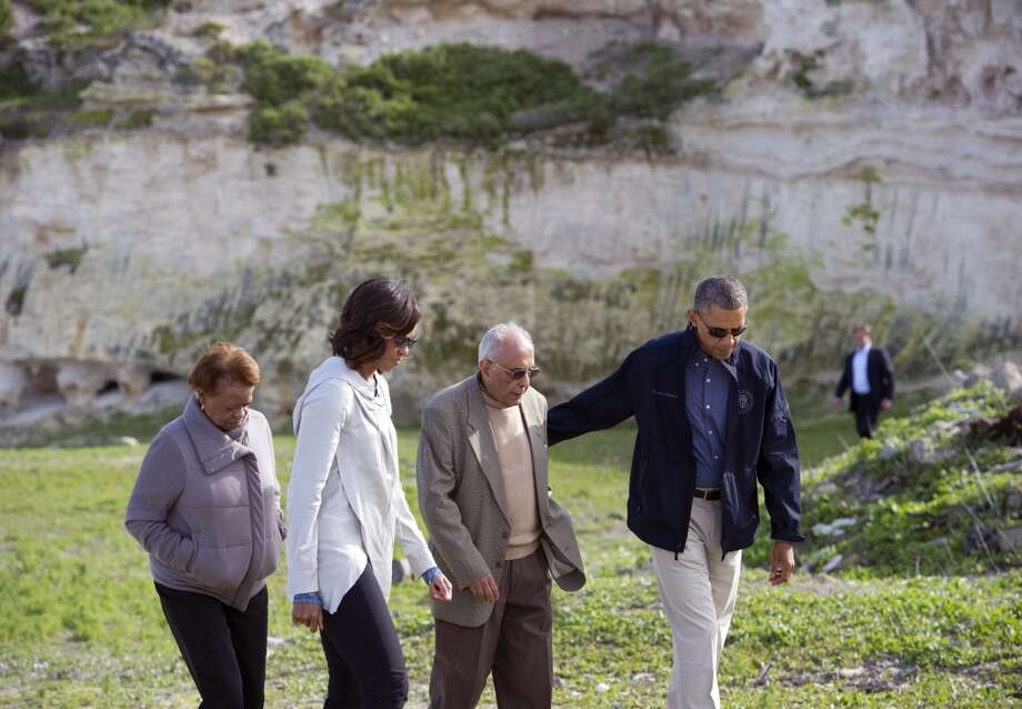 "US President Barack Obama (R), First Lady Michelle Obama (2L) listen to former prisoner Ahmed Kathrada with Michelle Obama's mother Marian Robinson as they tour the limestone quarry where prisoners worked on Robben Island off the coast of Cape Town, South Africa on June 30, 2013. President Barack Obama was ""deeply humbled"" by a visit to the cell where Nelson Mandela spent years as a prisoner, in a solemn homage Sunday to the critically ill hero he was unable to see in Pretoria.  AFP PHOTO / Saul LOEBSAUL LOEB/AFP/Getty Images"